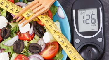 Glucose meter with sugar level, centimeter and fresh prepared greek salad. Diabetes, slimming, healthy lifestyles and nutrition